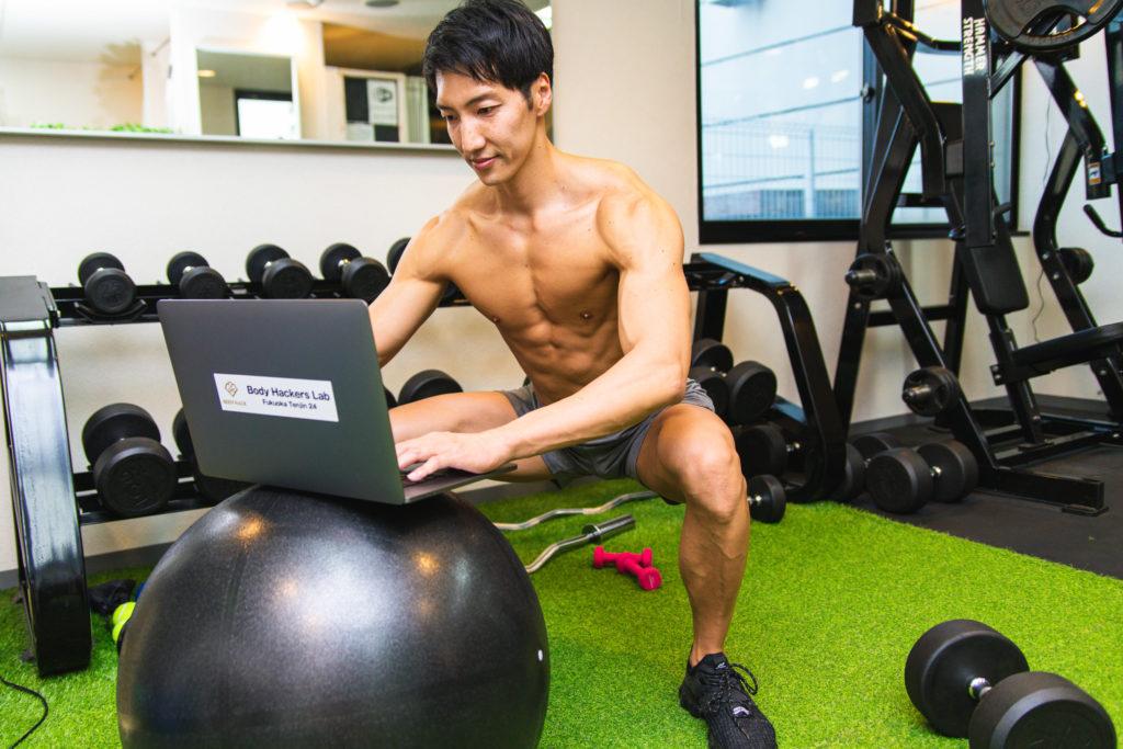 ジムで鍛えながら事務作業をするマッチョ/reference photo for drawing muscles/work at gym@著作権フリー 画像 筋肉