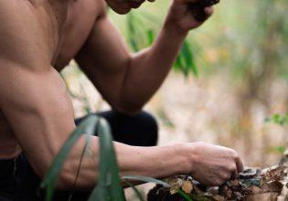野生の焼き芋食べながら野生のキノコを食べようとするマッチョ(縦写真)@フリー素材 マッチョ