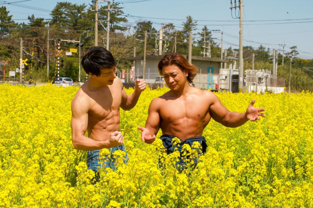 菜の花の方向性を話し合うマッチョ@フリー素材 筋肉