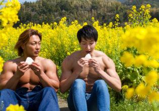 菜の花畑でおにぎりを食べるマッチョ@フリー素材 筋肉