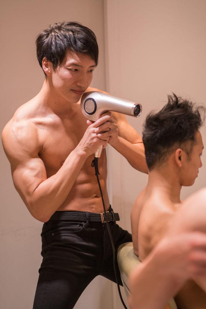 ドライヤーに集中するアシスタントマッチョ(縦写真)/reference stock photo muscle beauty salon blow dryer@写真 マッチョ
